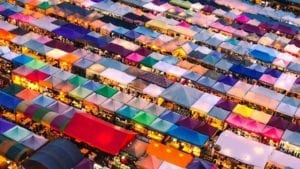 Colored tents at a market ar illuminated during the evening in Thailand.