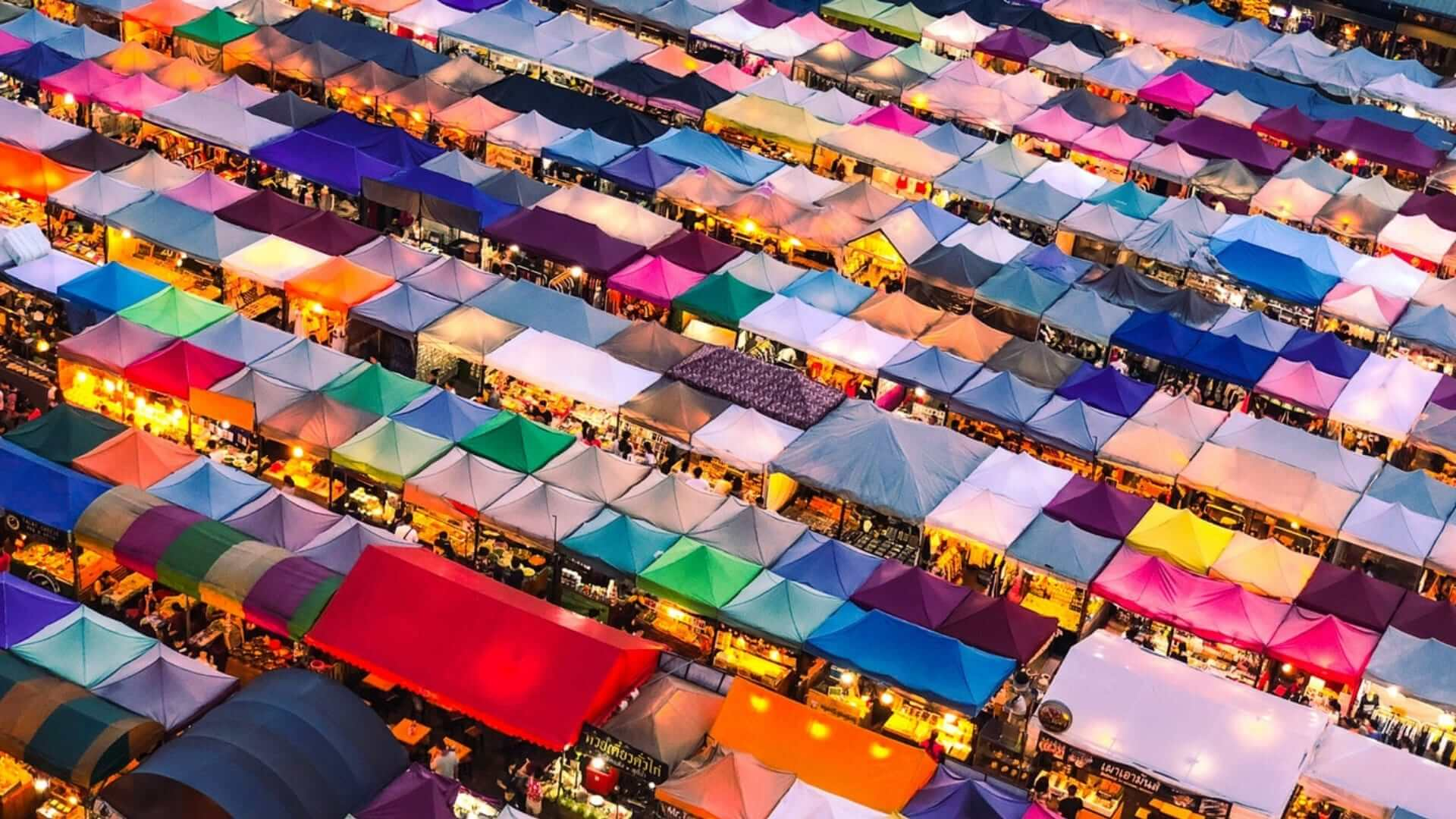 Colored tents are illuminated at a market during the evening in Thailand.