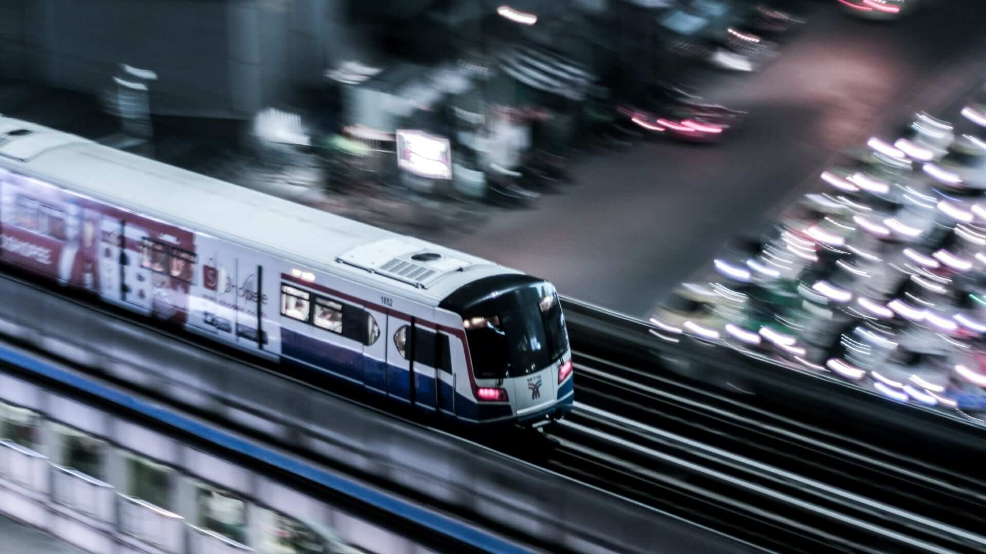 A skytrain is driving fast over a high railway in Bangkok.