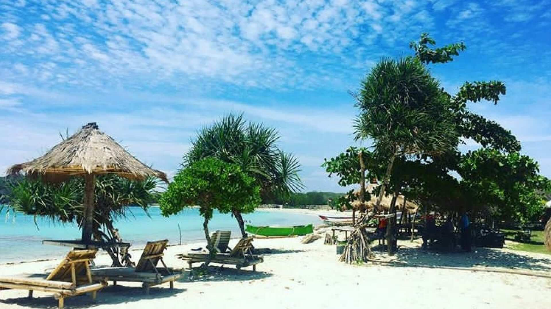 View of beach beds, parasols and trees on the beach on a sunny day in Lombok.