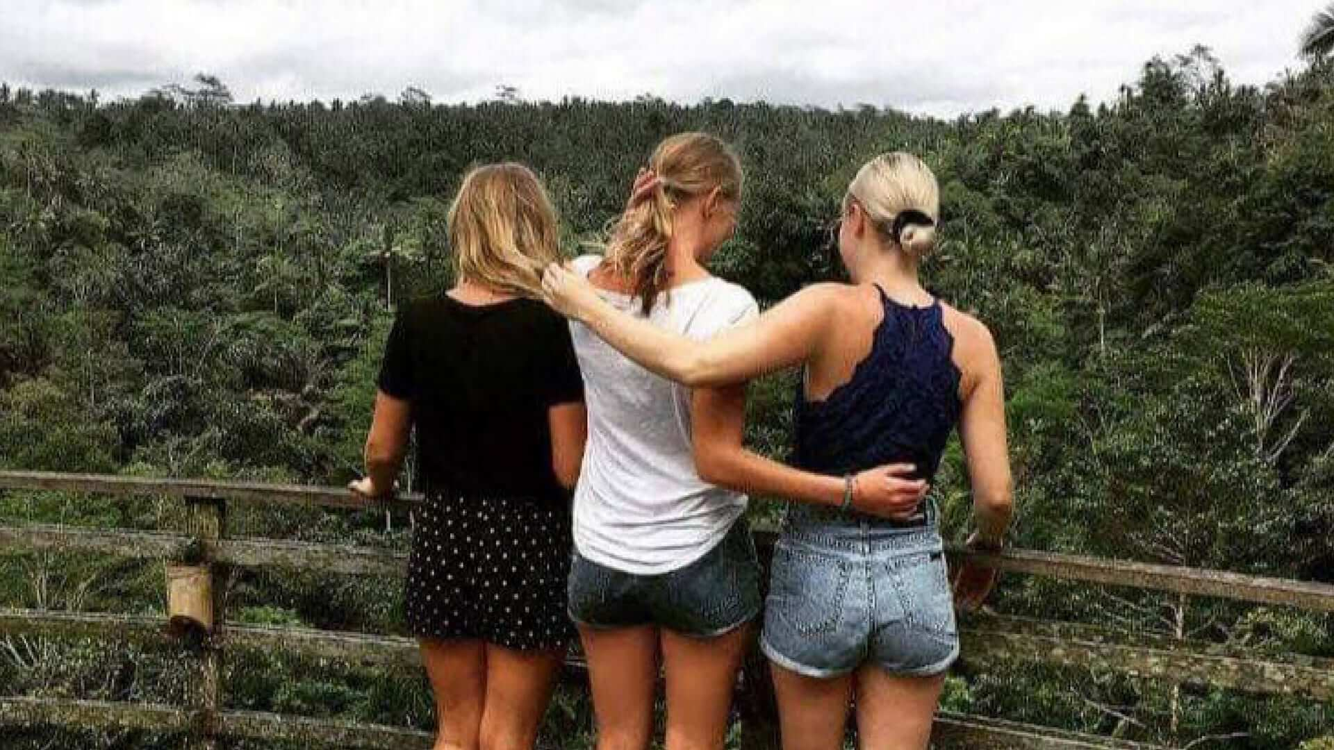 Back view of three blond girls looking over trees in Ubud.