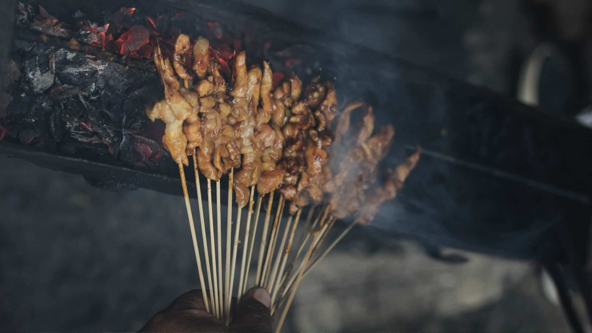 A person is holding sticks of satay on a smoking grill in Bali.