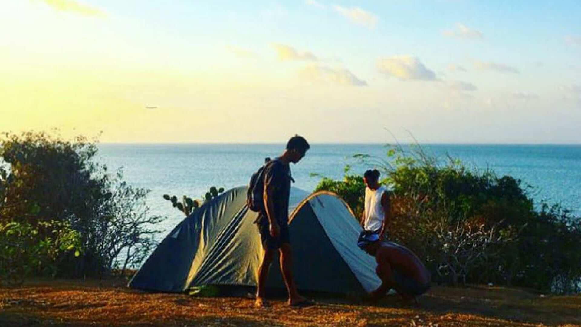 Three men pitching a tent during sunset at JImbaran Beach.