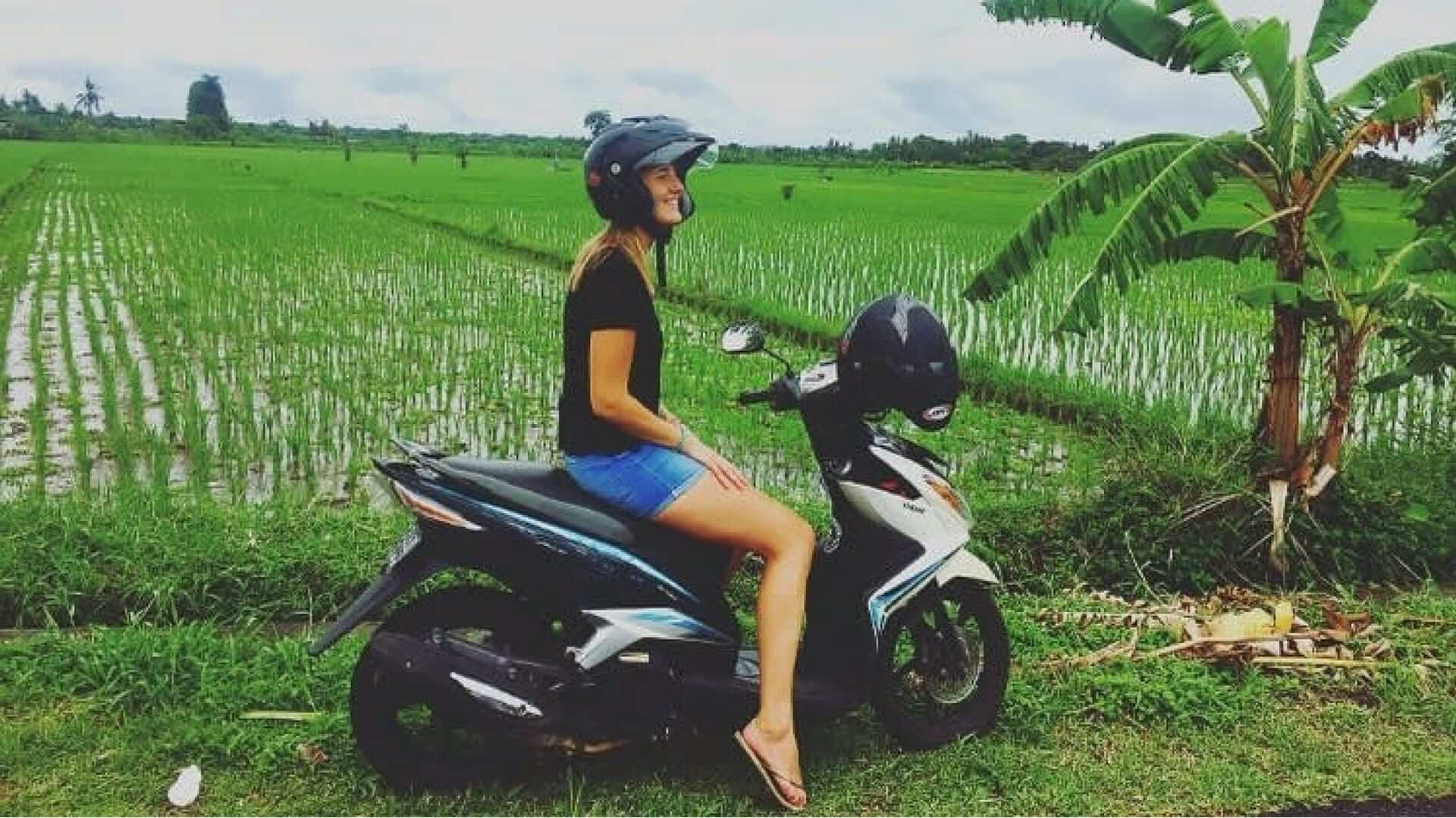 Girl on a scooter in front of rice fields in Tanah Lot.