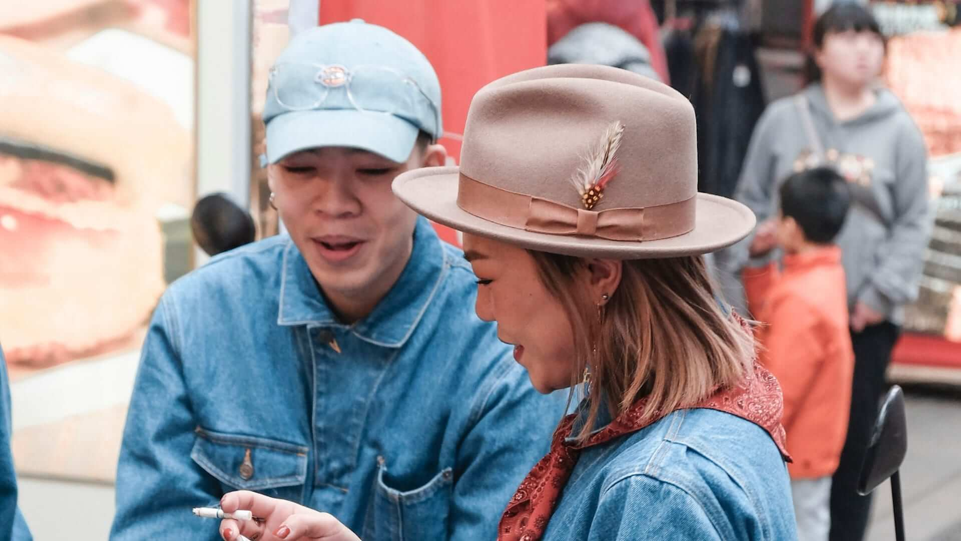 Two girls wearing denim jackets and hats are talking to eachother and laughing in Taiwan.