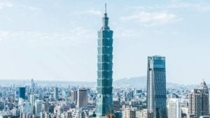 A big tower surrounded by other buildings during a day in Taipei.