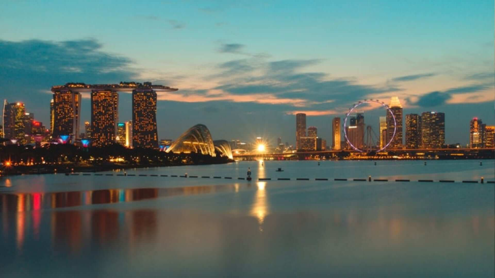 A picture of a bay surrounded by illuminated buildings during the evening in Singapore.