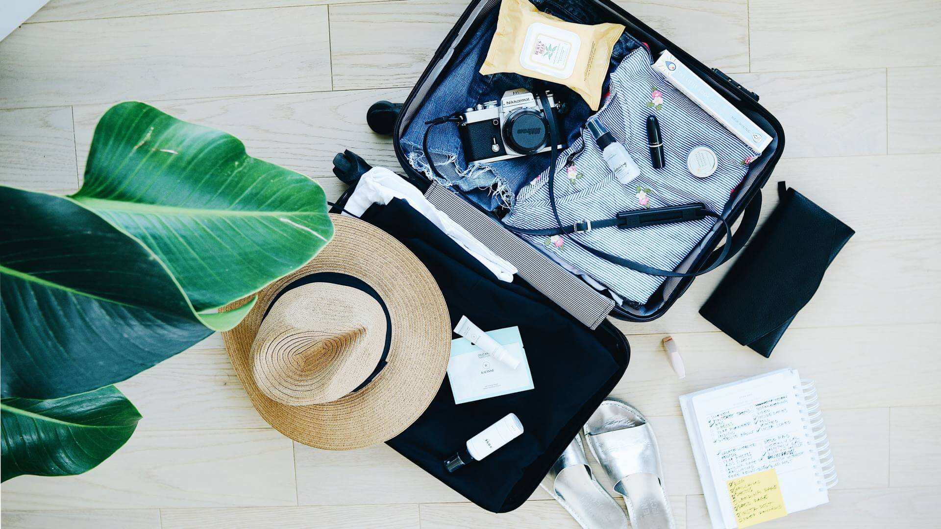 A bag filled with travel essentials on a white wooden floor