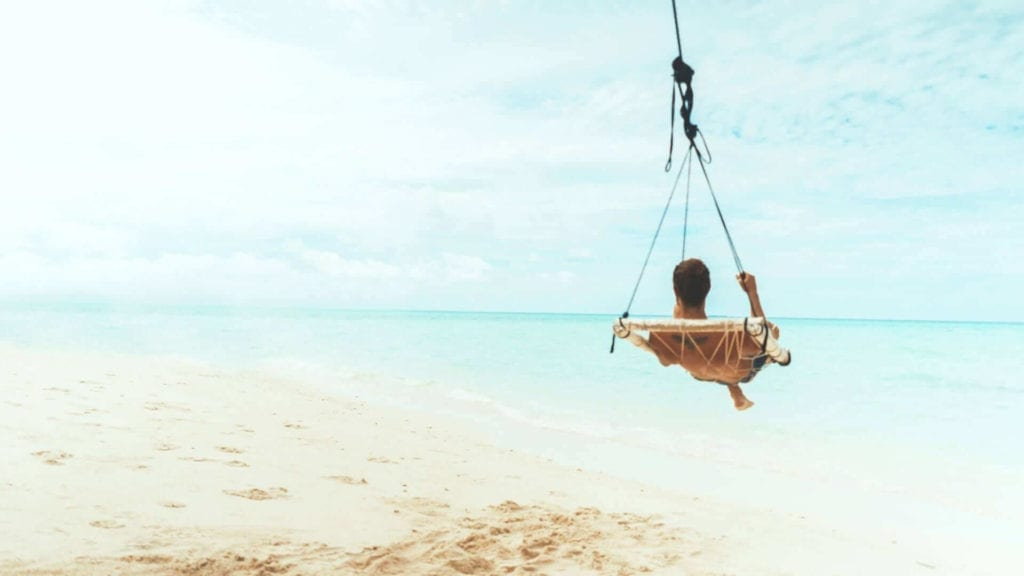 A man is sitting on a swing on a tropical island