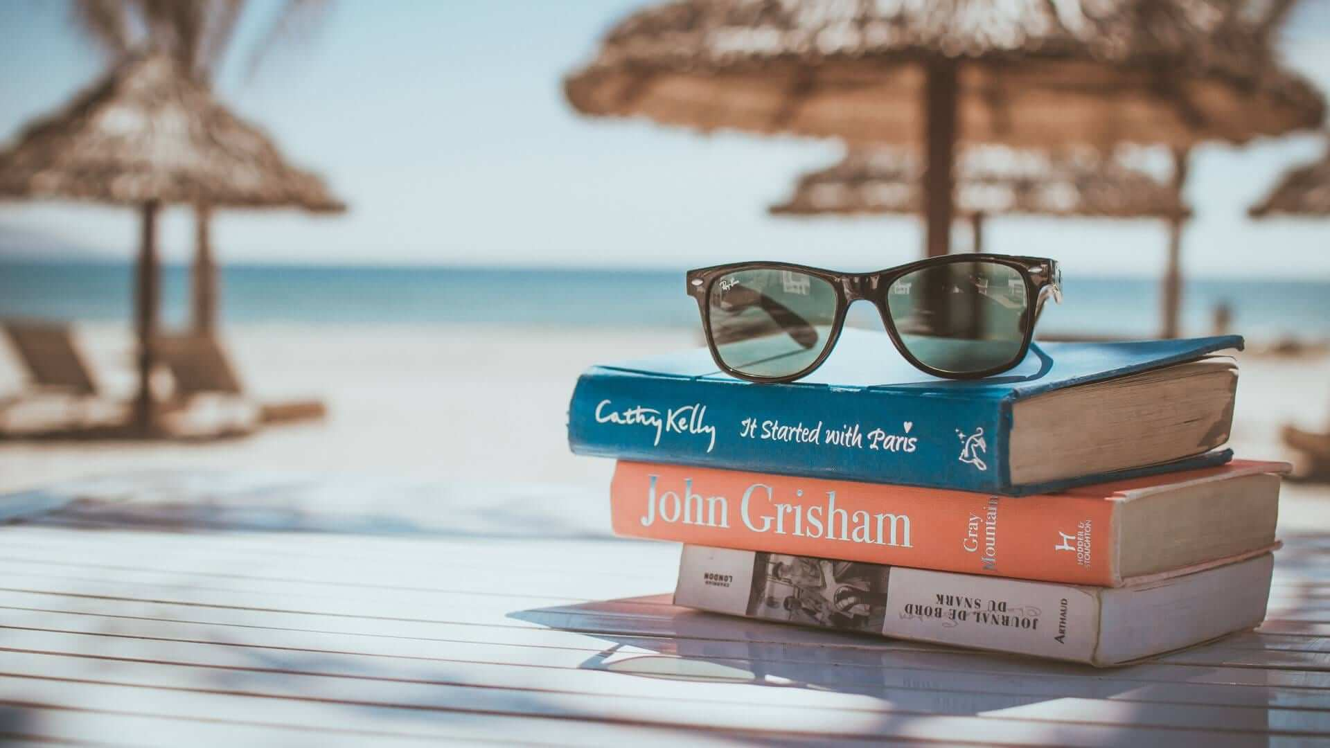 Three books and sunglasses in the shade on a table at the beach