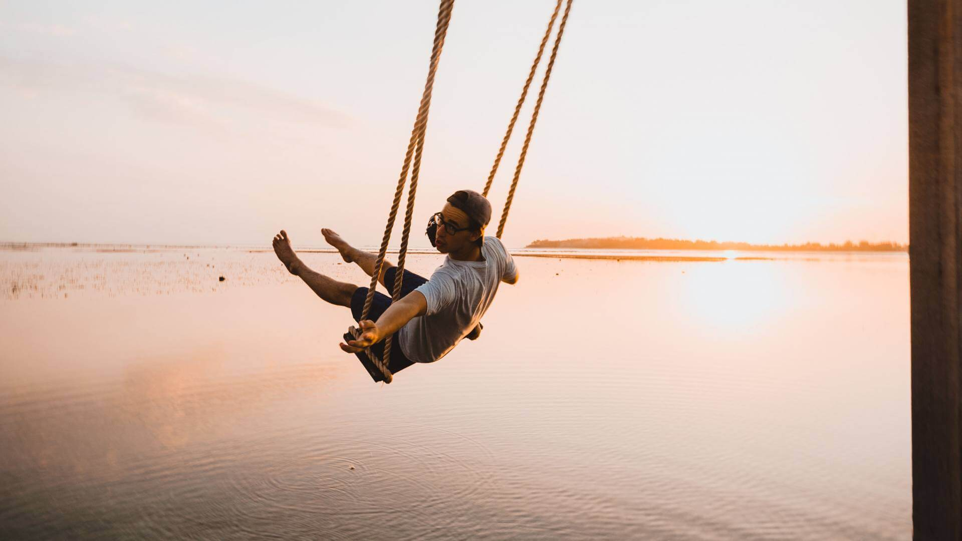 Man is sitting on a swing above water during sunset