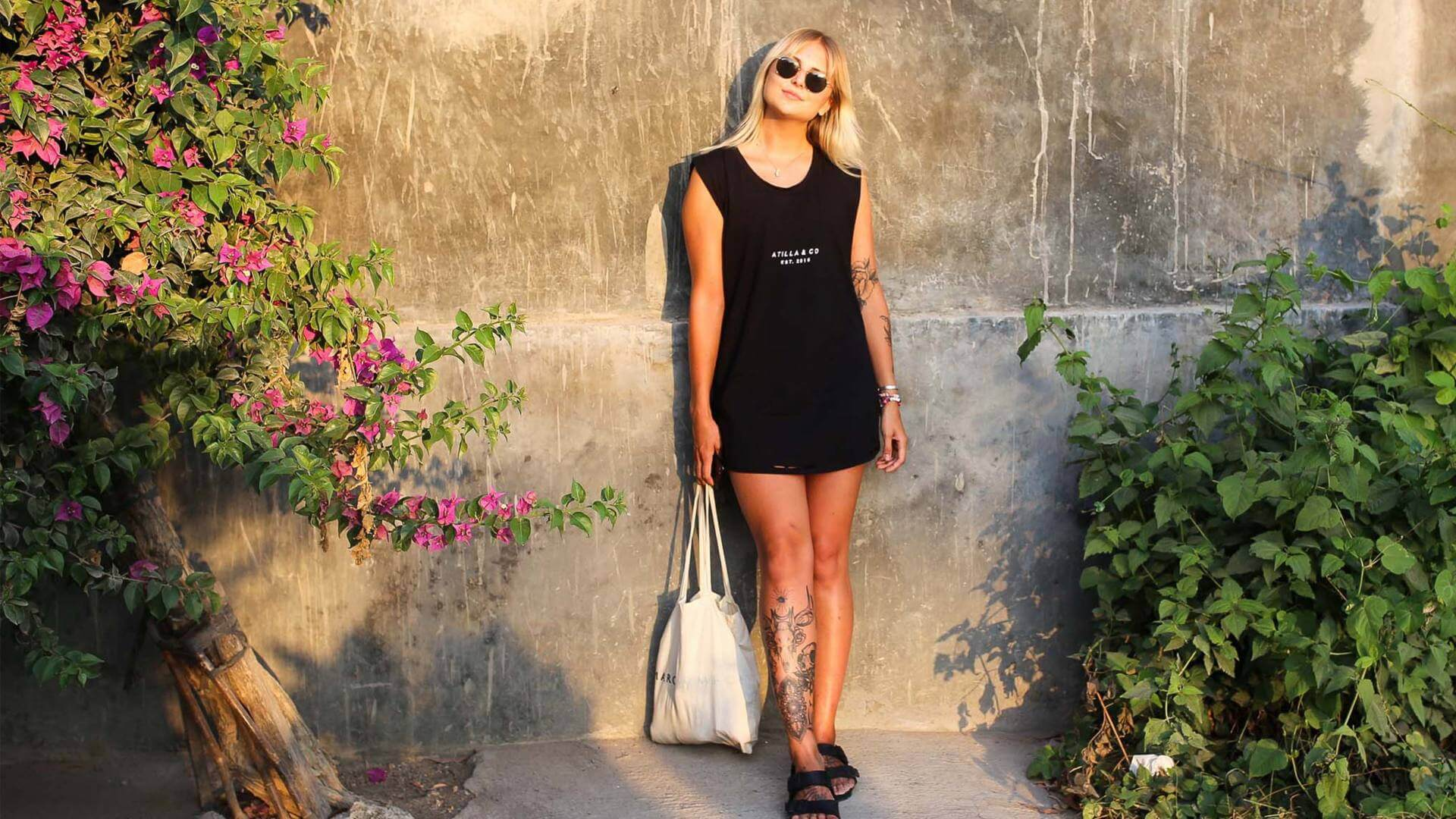 Blonde girl with sunglasses and black shirt is leaning against a wall in Bali.