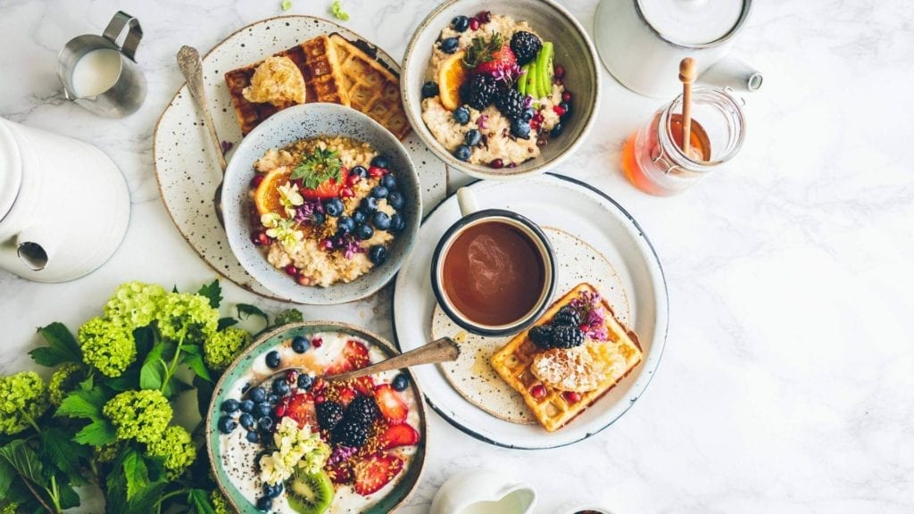 Fruits and pancakes on white plates and a cup of coffee