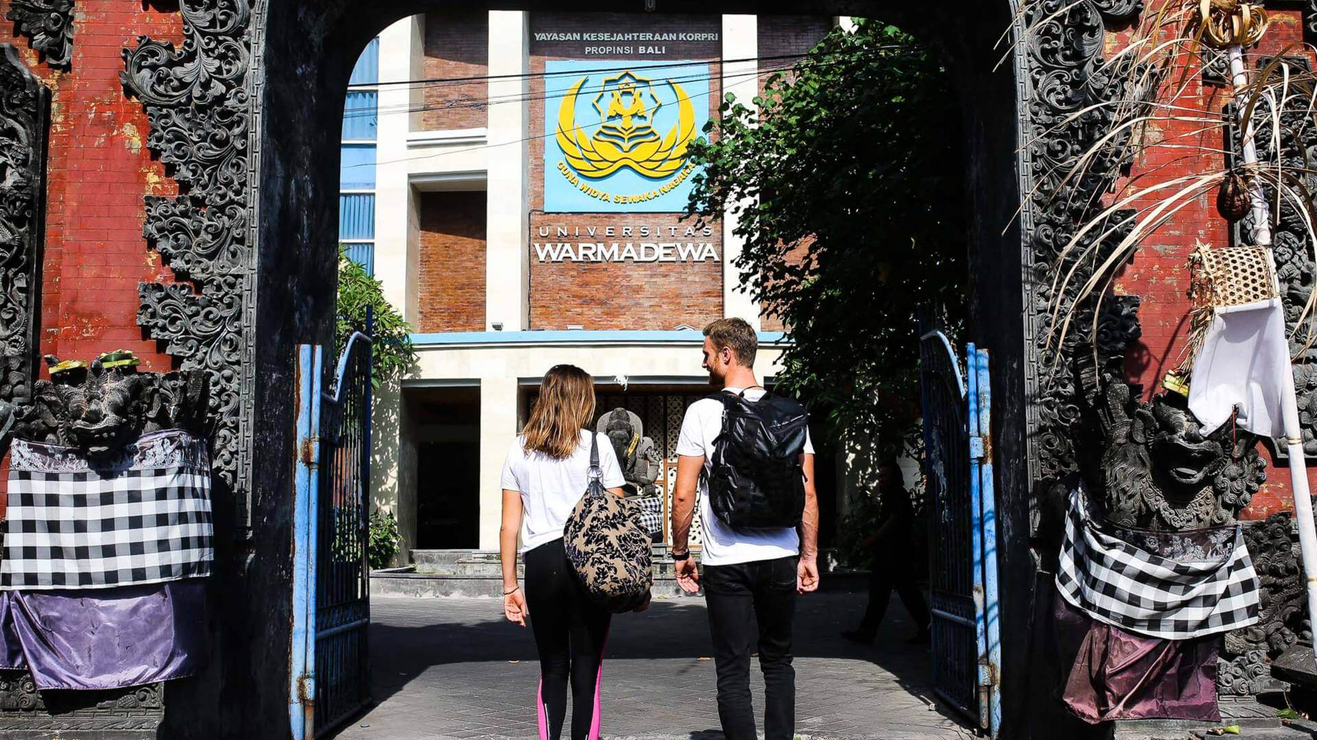 Two persons are walking through a gate with backpacks on their backs