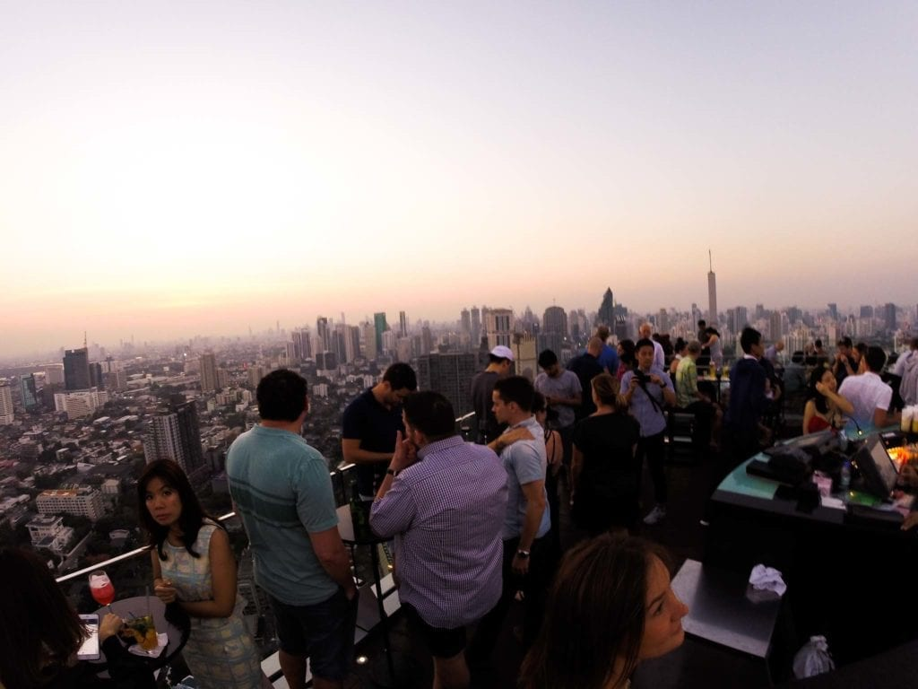 A group of people is standing on a rooftop bar with a view of many buildings in Bangkok