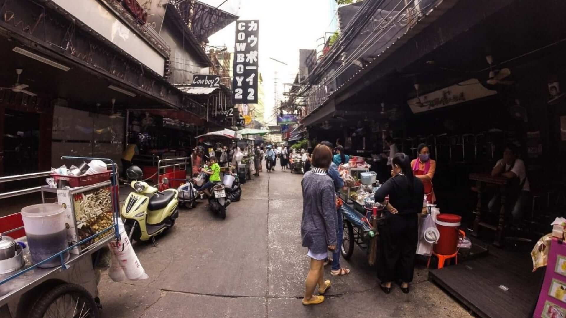 People are standing next to carts waiting for food in a street in Bangkok.