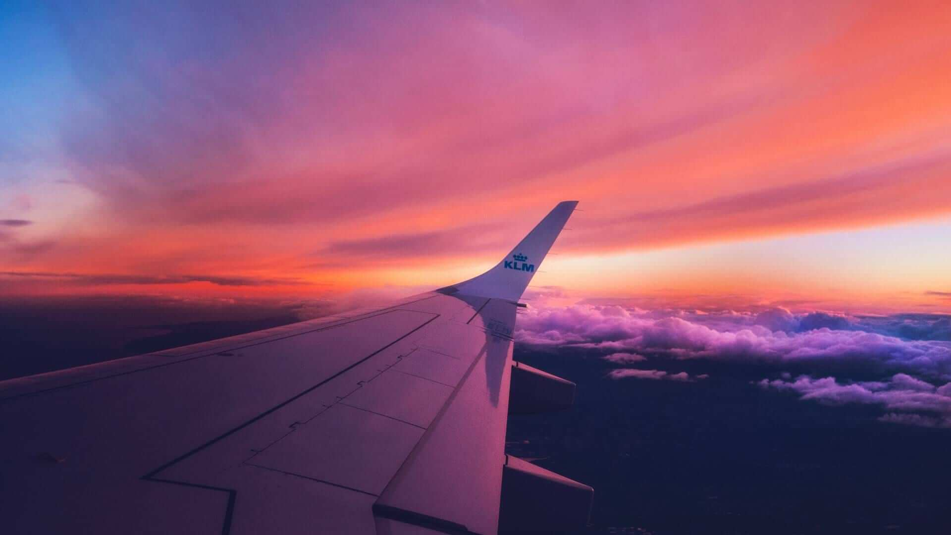 An airplane wing and a pink sky