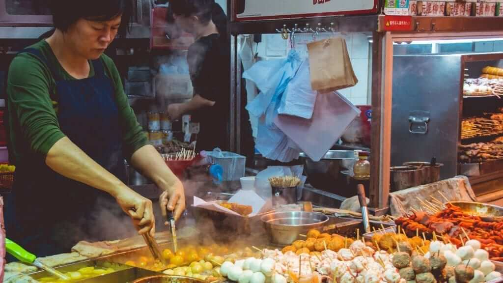A woman is cooking on the streets of bangkok