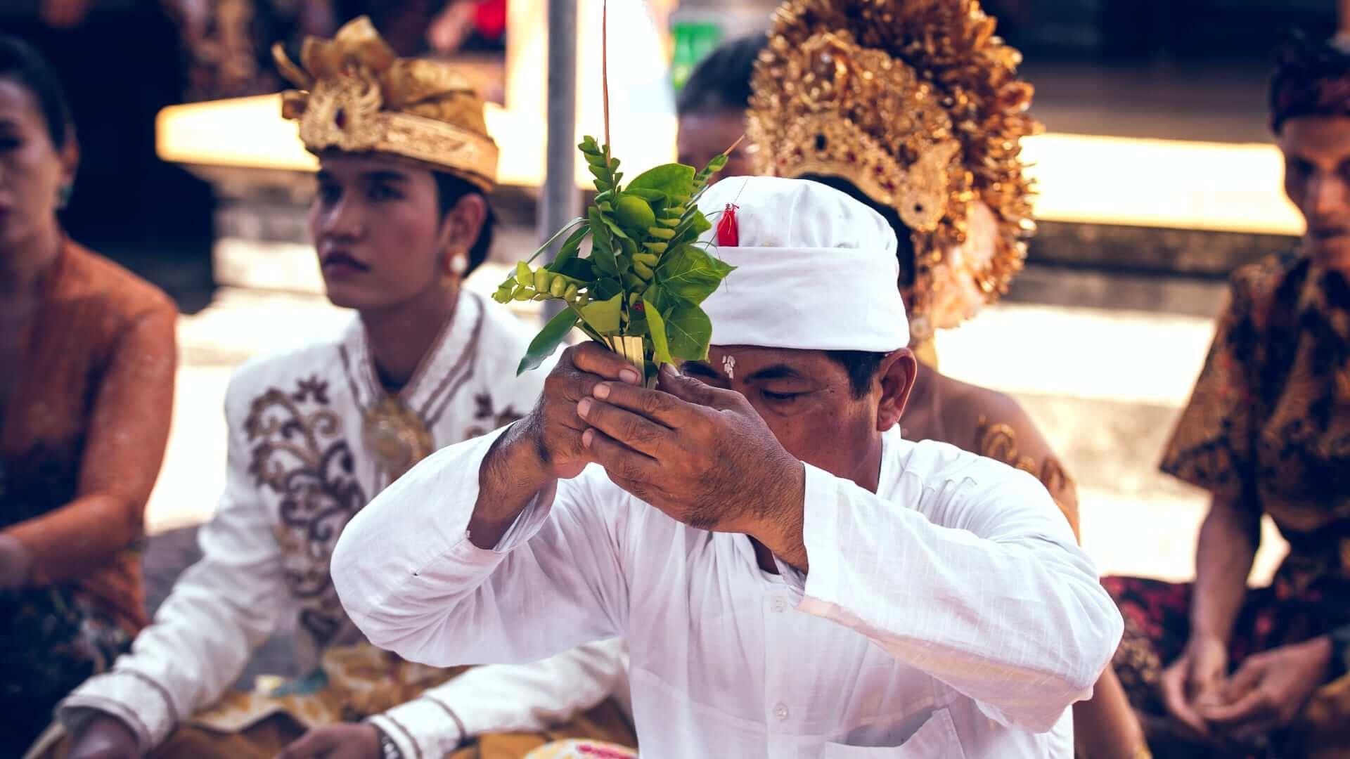 Balinese men and women praying during a religious event.