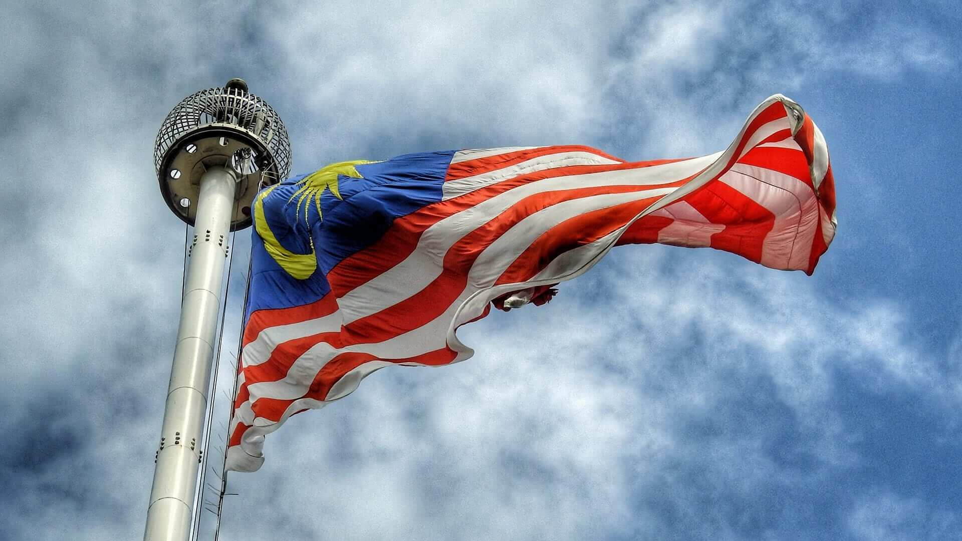 Flag of Malaysia flying, cloudy skies in background