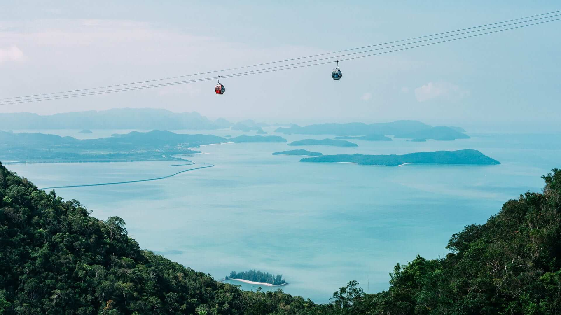 view of ocean and islands from high up. two cable cars going across the sky
