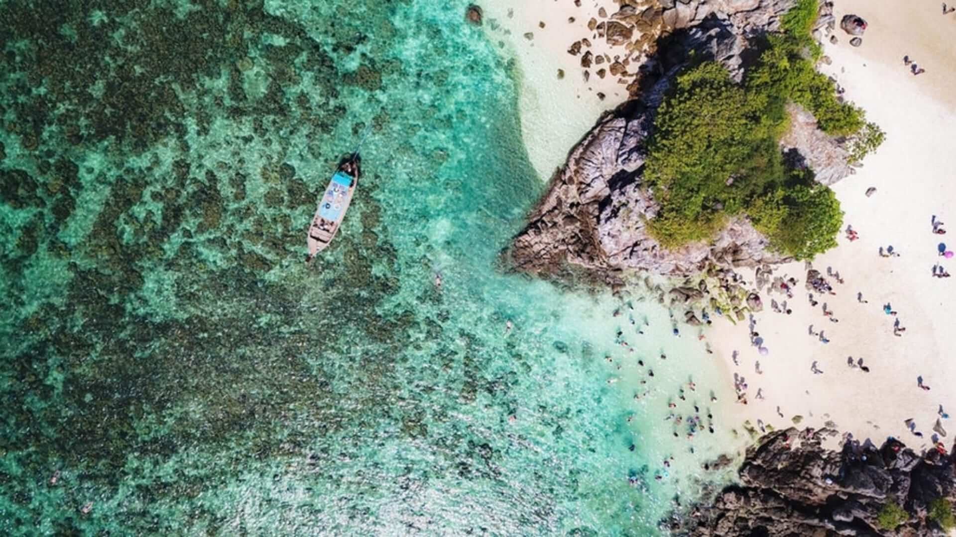 A picture from above of a boat in a blue sea near a white beach in Thailand.