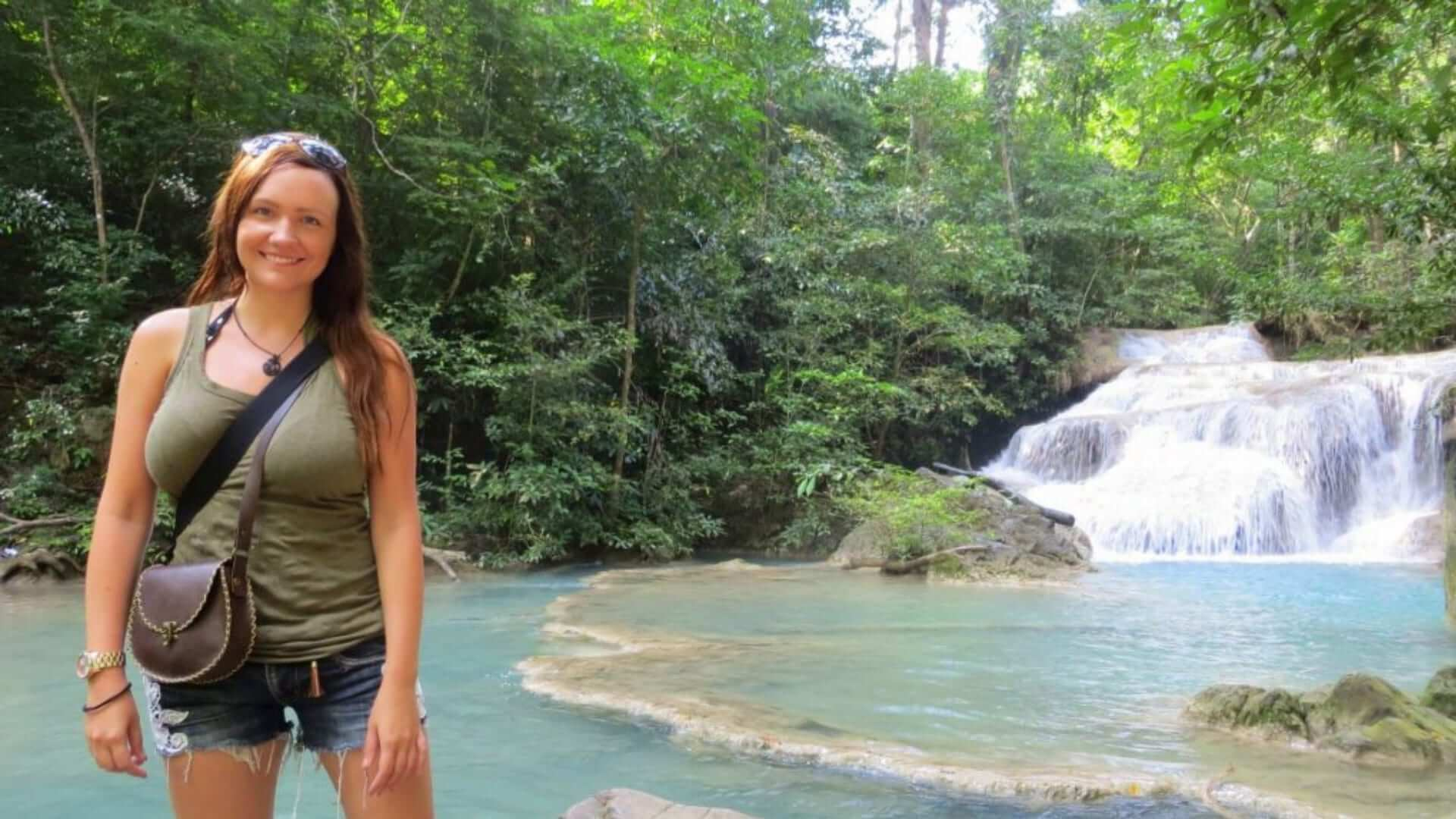 A girl is standing in front of a waterfall in Thailand.