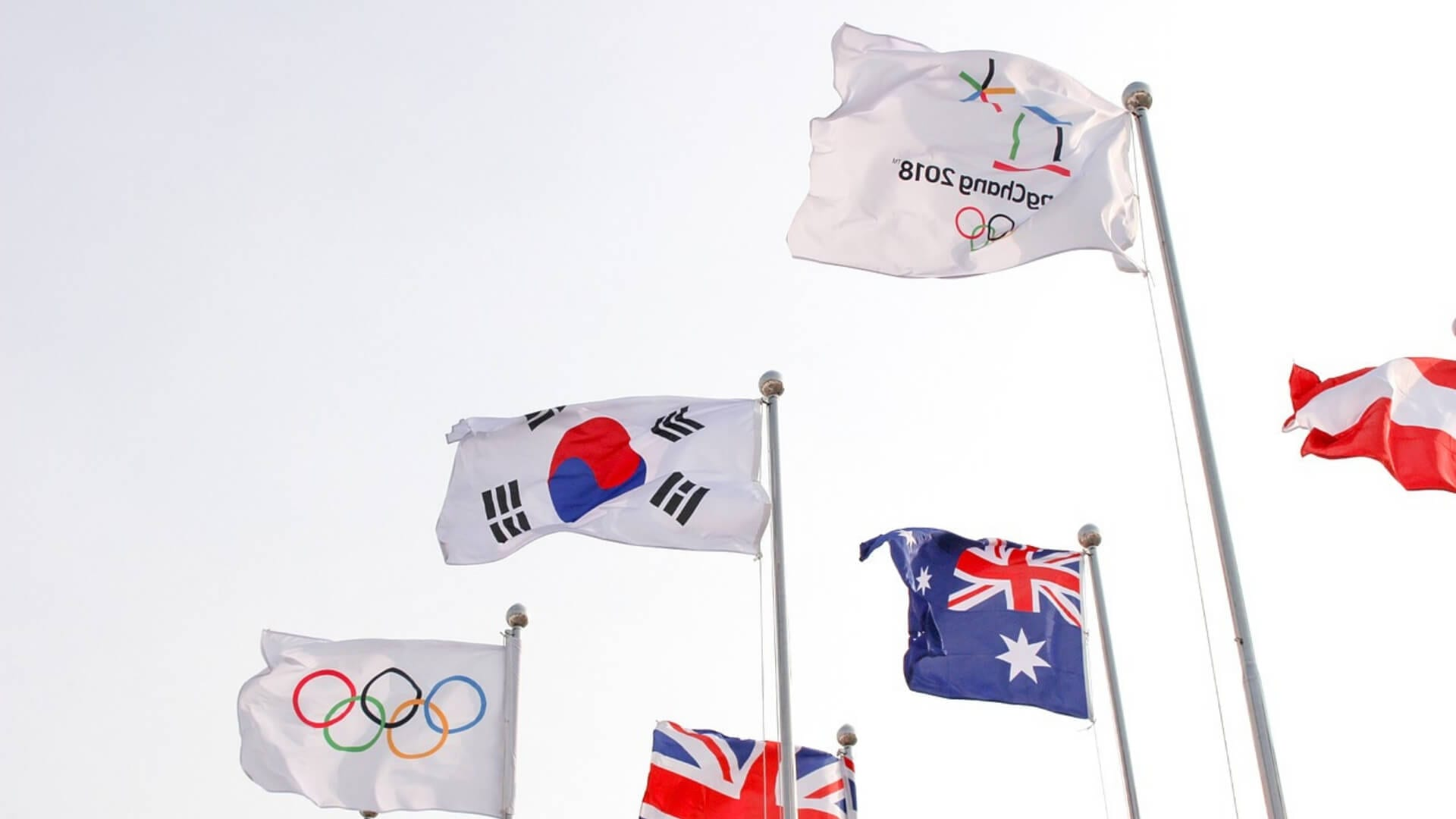 Five flags are fluttering in the wind during the olympic winter games in Korea.
