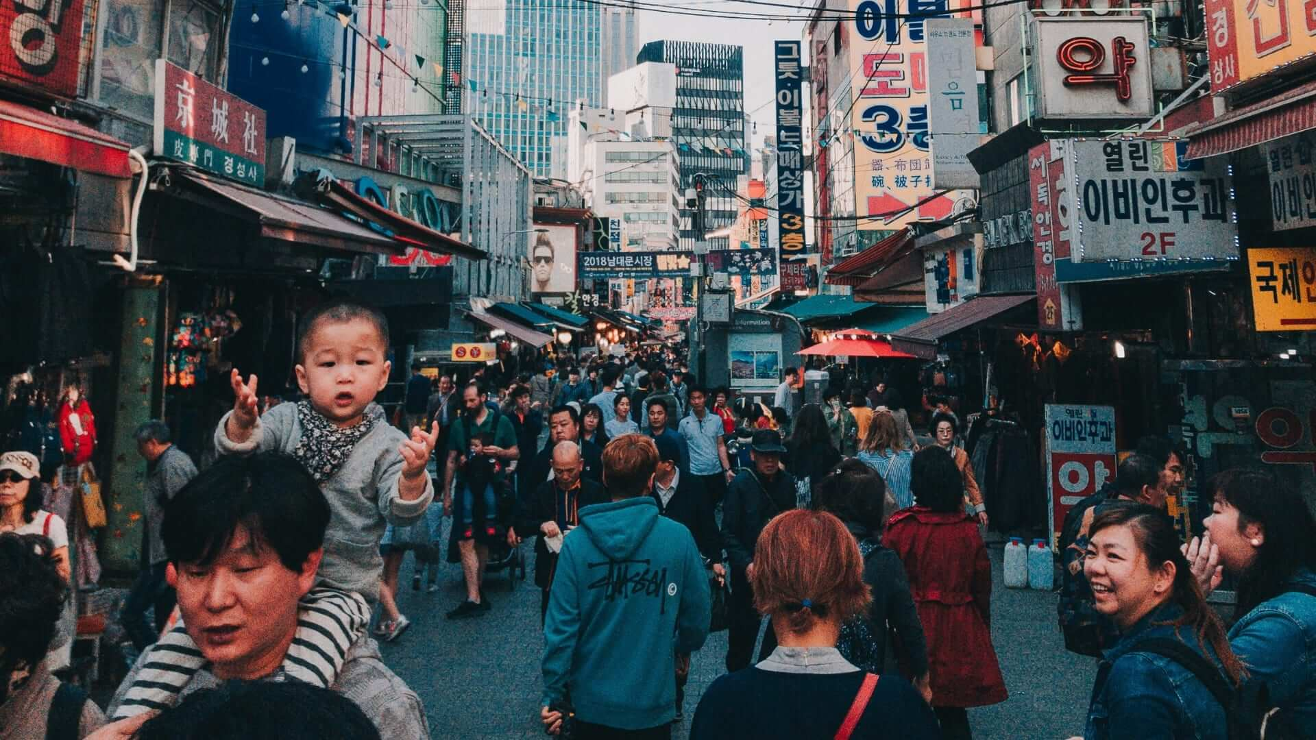 A baby is sitting on someone's shoulder while they are walking through a crowded street in Korea.