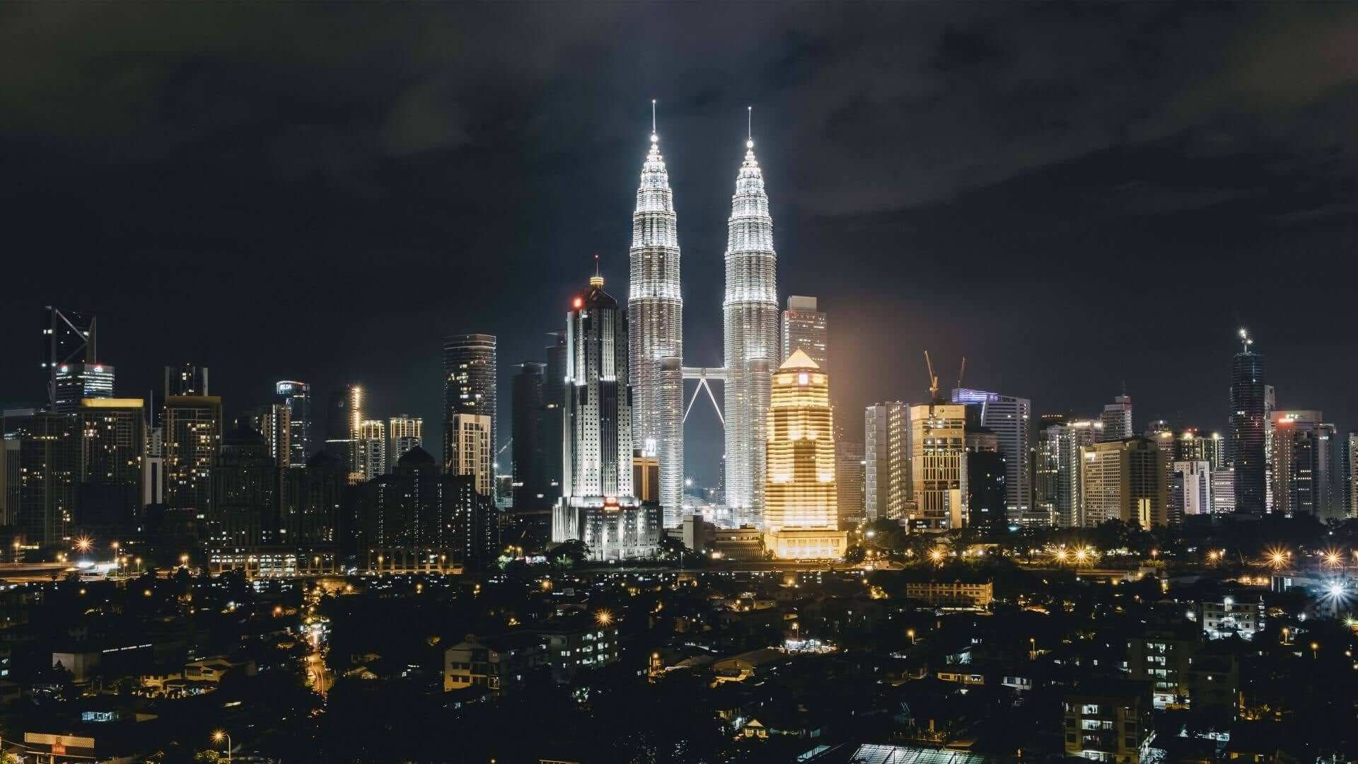 Night view of the brightly lit Petronas Towers in Kuala Lumpur.