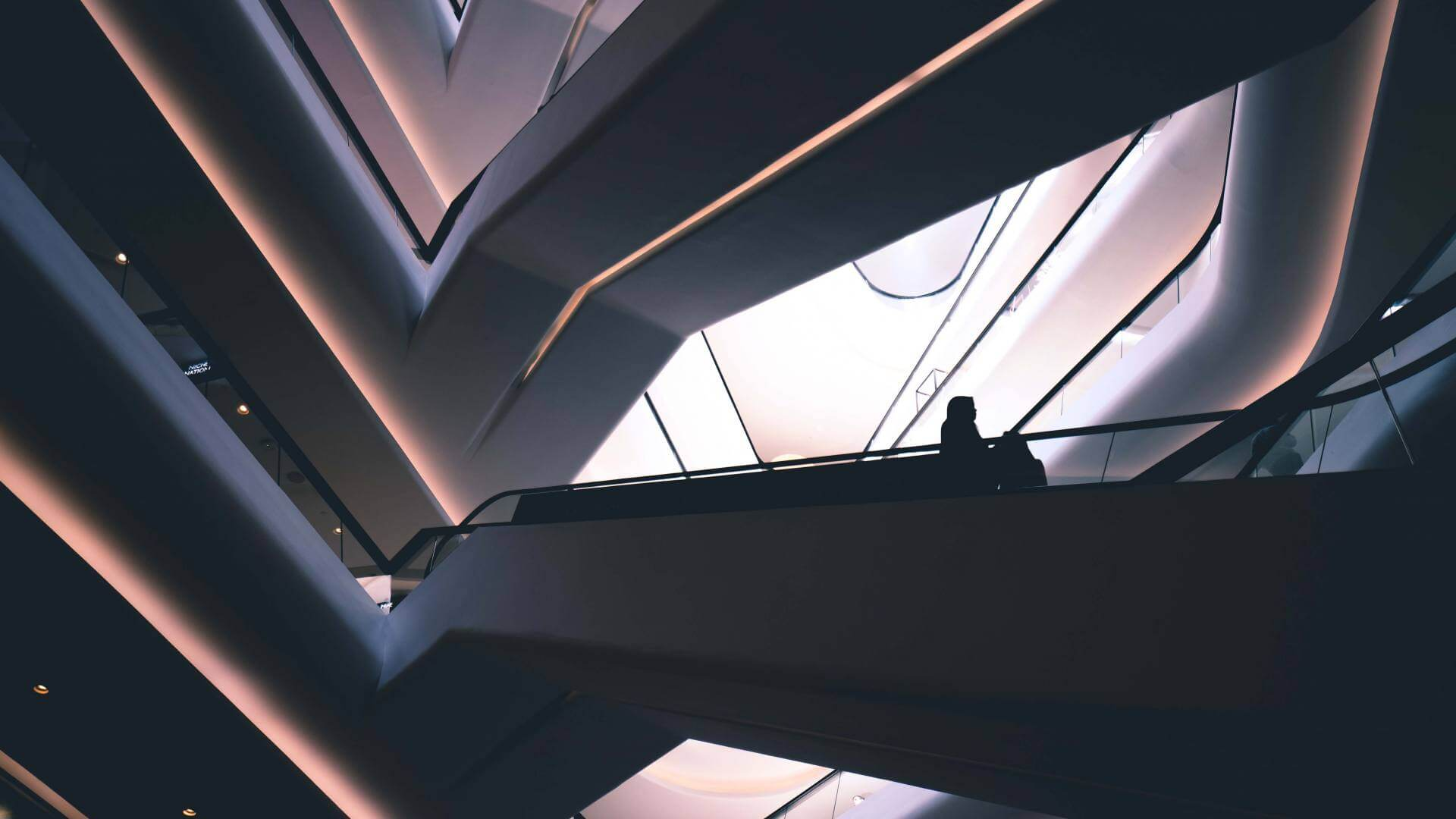 Silhouette of a person standing on an escalator in a shopping mall in Kuala Lumpur.