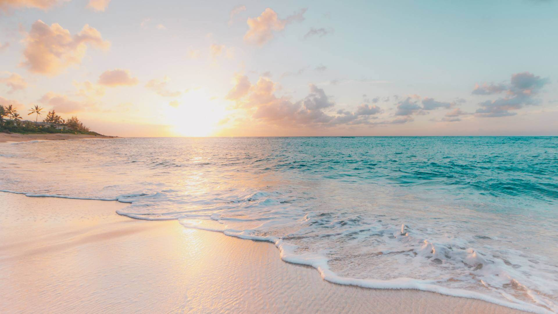 White sand beach and clear blue water during sunset