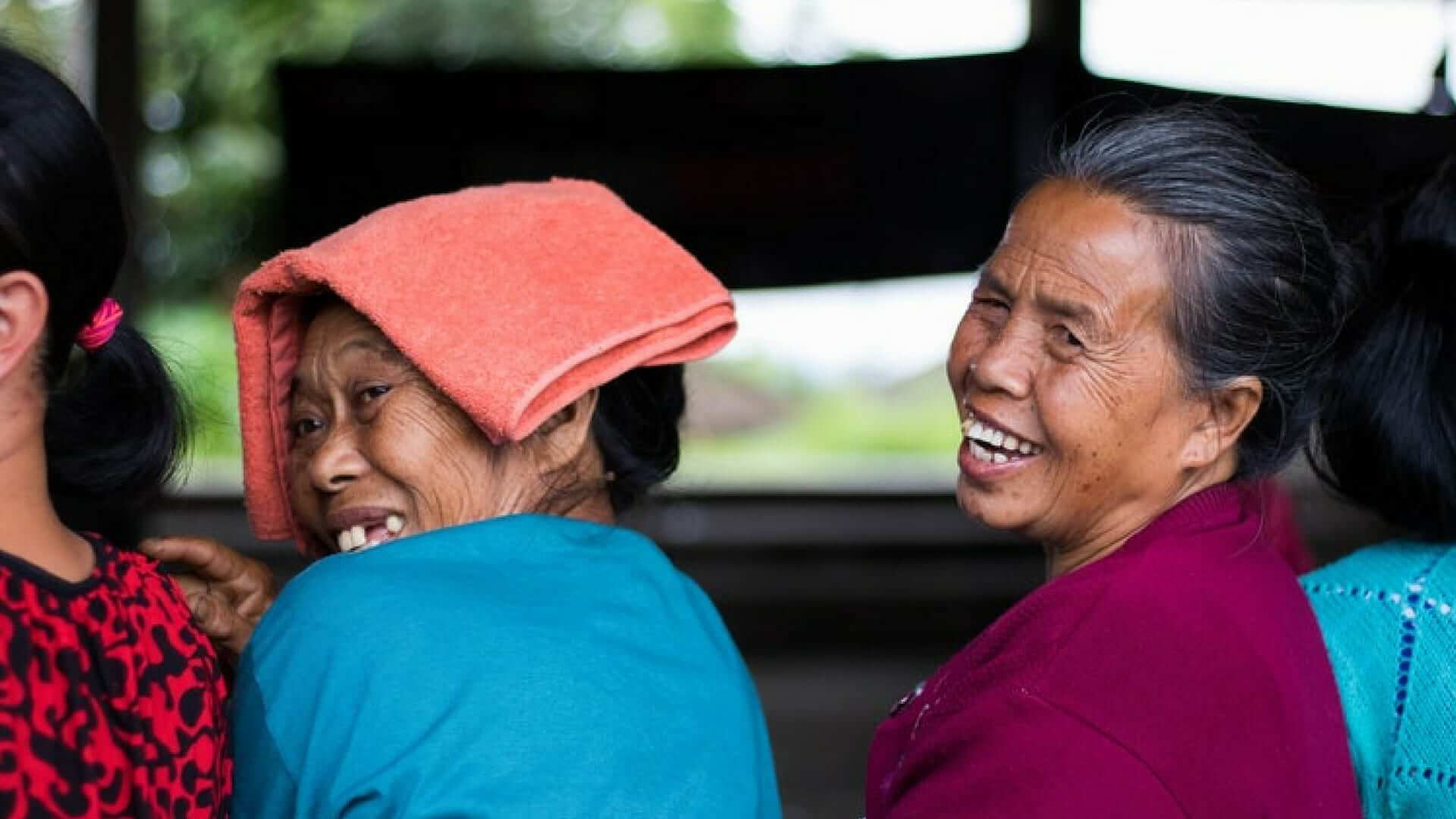 Two Indonesian women are smiling over their shoulder in the camera.