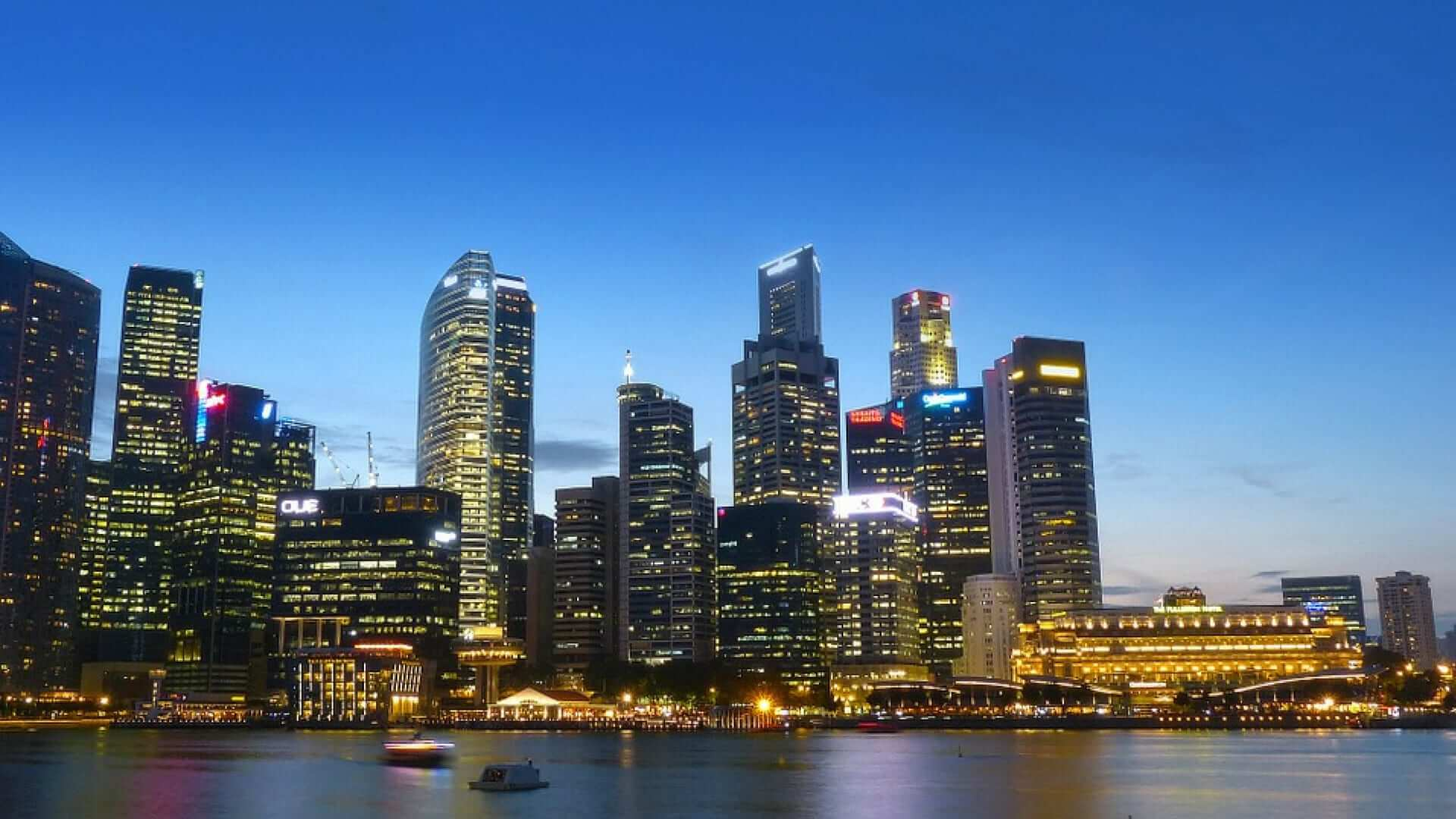 Illuminated tall buildings on the waterfront during the evening in Singapore.