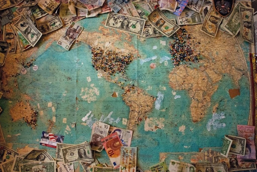 Different currency bills on top of a world map.