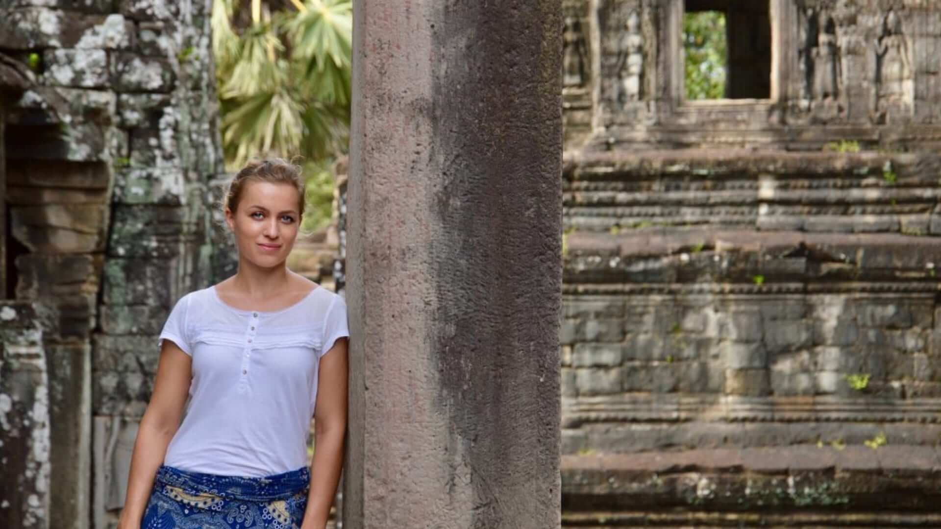 A girl is leaning against a tree in front of a temple in Phuket.