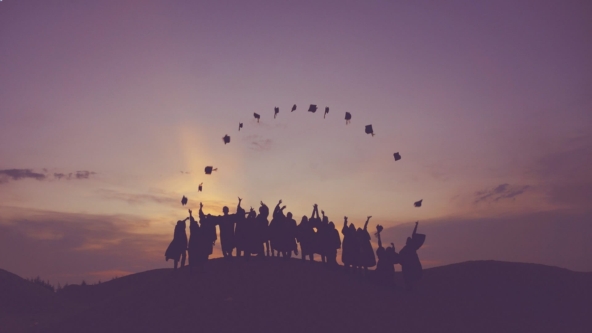 A group of people is standing on a hill and throwing their hats in the air in a cirlce during sunset in Asia.