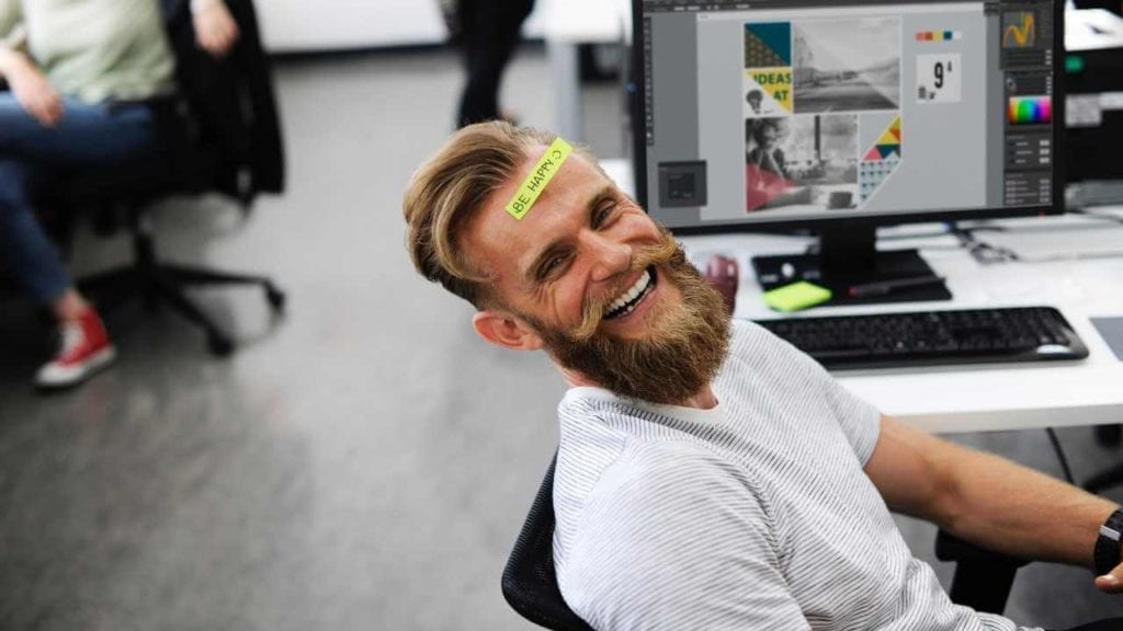 long beard person leaning on a chair with a be happy post it stuck on their forehead