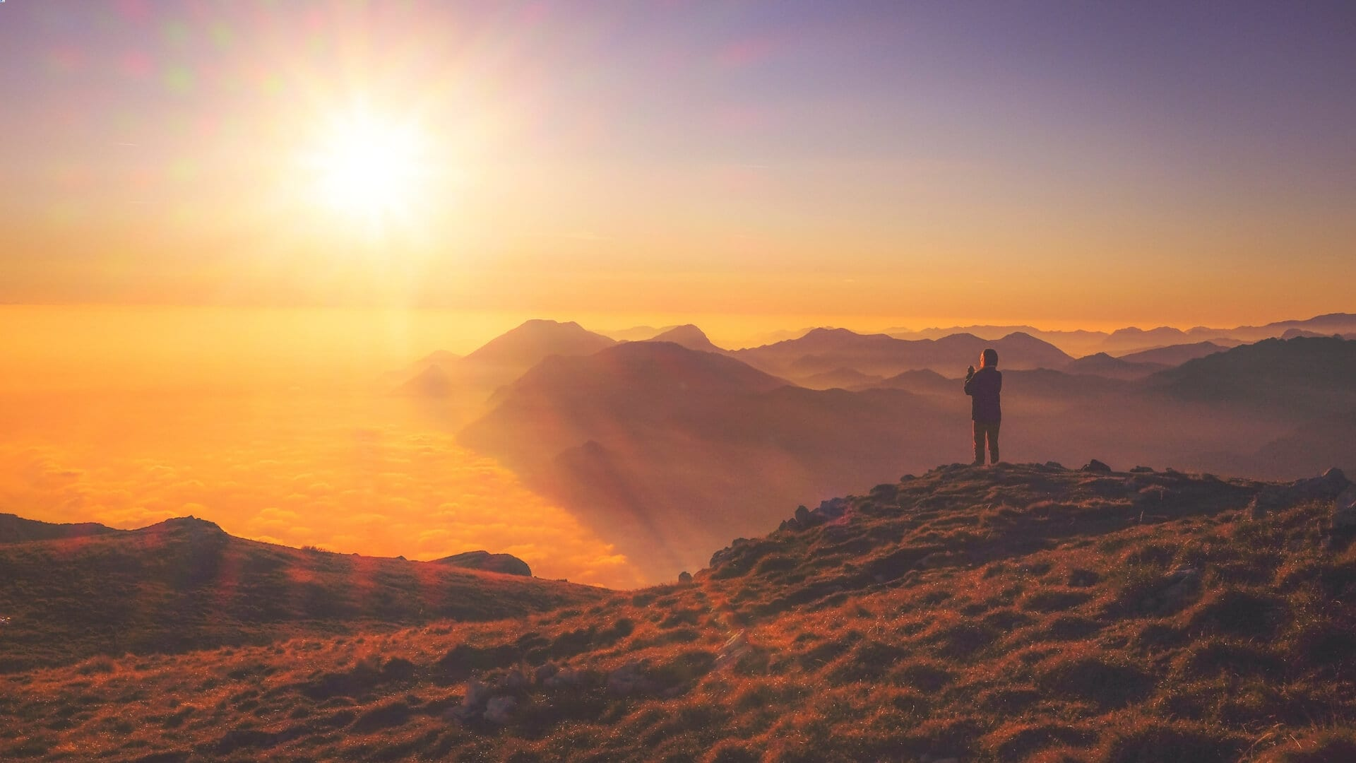 A person is standing on a mountain during sunrise in Asia.