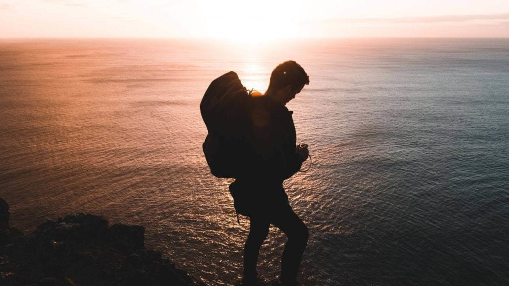 A man is standing on a cliff with a backpack during sunset