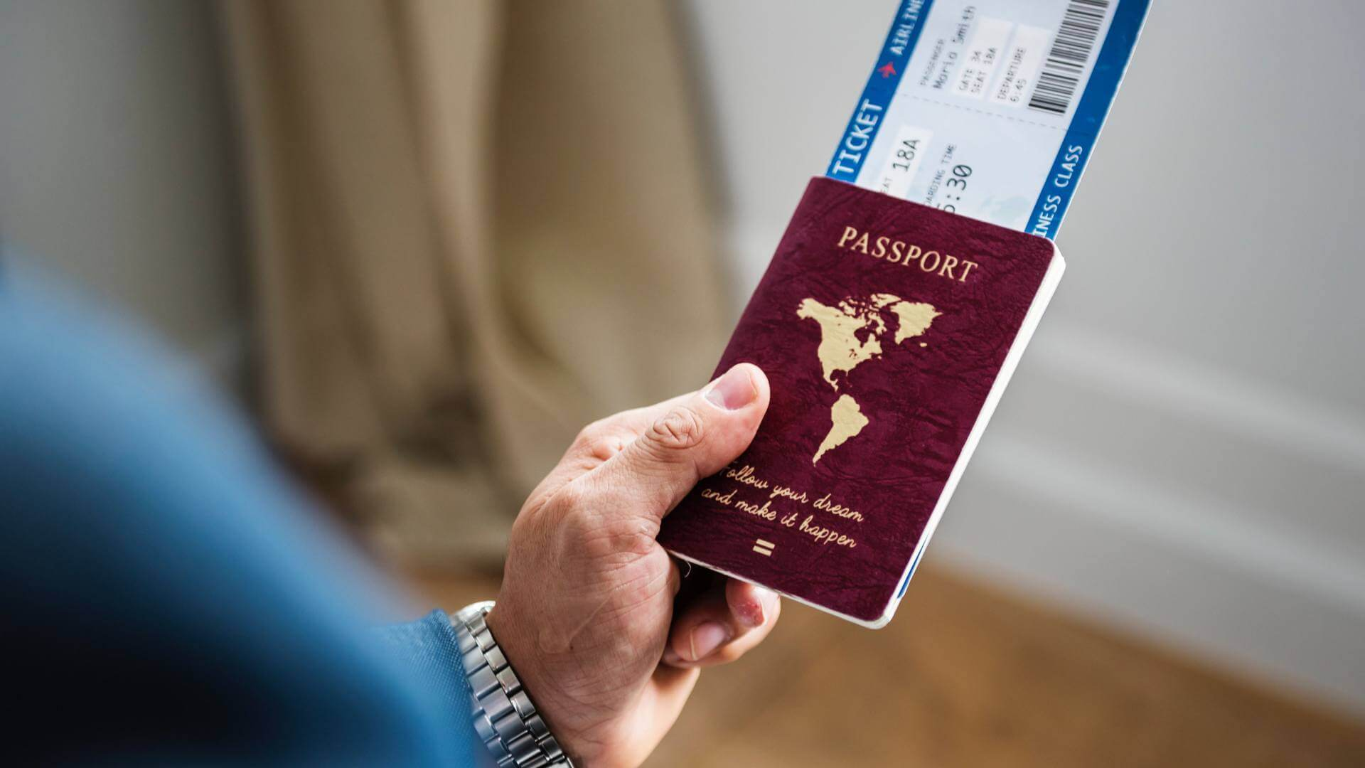 Someone holding a passport with a flight ticket inside
