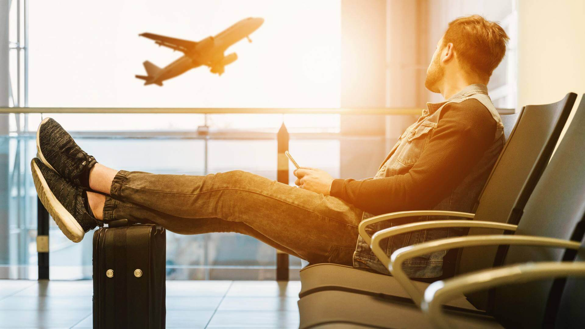 A man is sitting with his suitcase watching a plane flying outside the window.