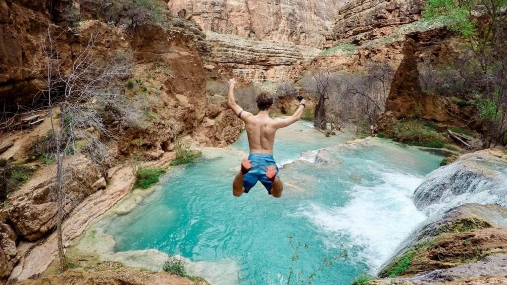 A man is jumping into the water from a cliff.