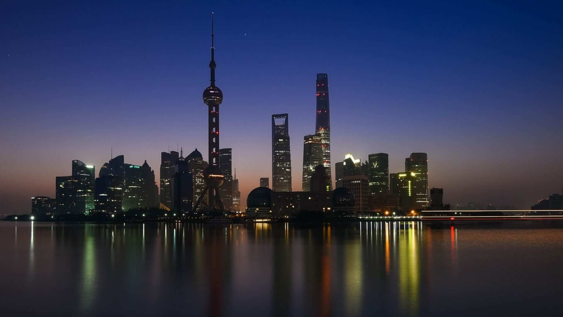 Illuminated buildings are reflecting on water during night in Shanghai.
