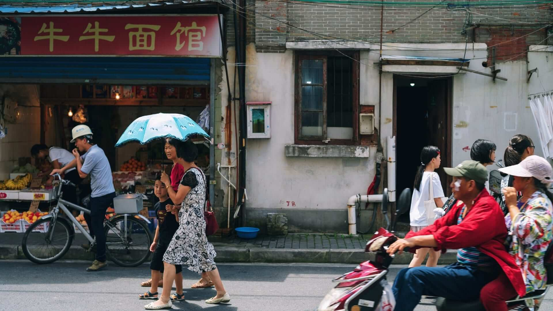 People are walking and driving a scooter and a bike on a street with a small Chinese fruit shop in it in Shanghai.