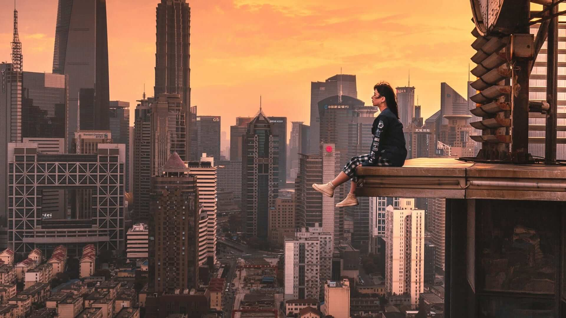 A girl is sitting on a protrusion of a building looking over the city during sunset in Shanghai.