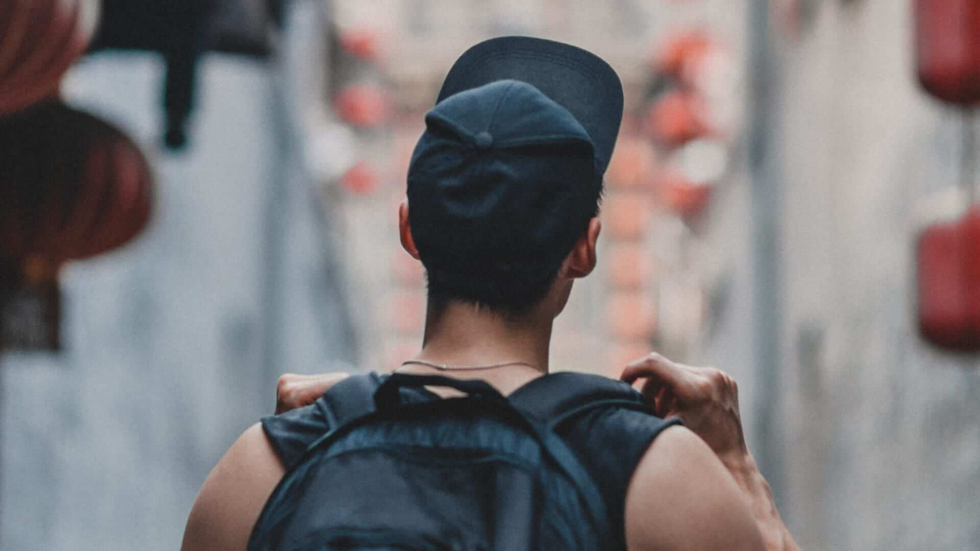 A boy wearing black clothes, a black backpack and a black cap is walking through a street in China.