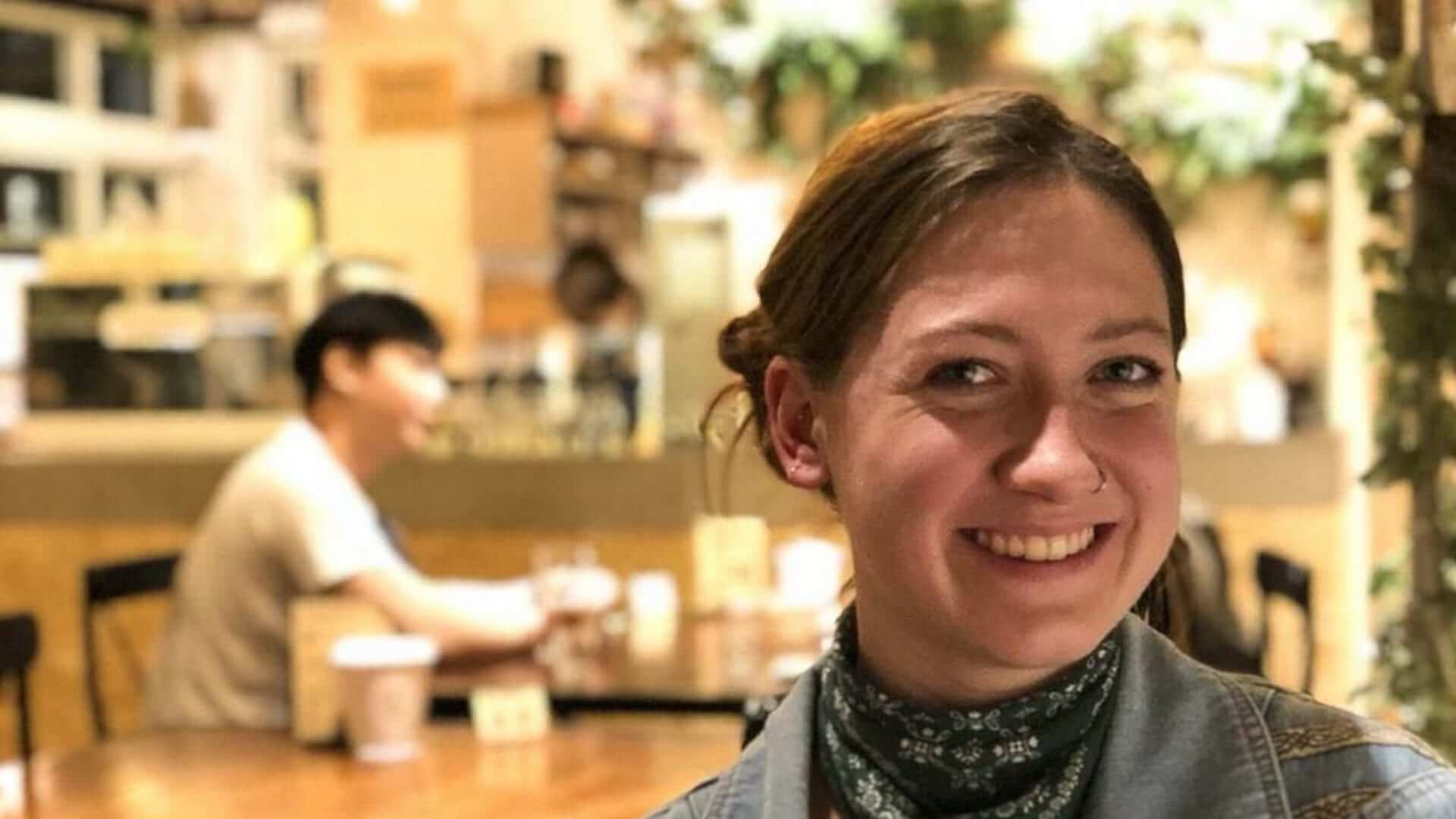 A student with a nose ring is smiling in a restaurant in Taiwan.
