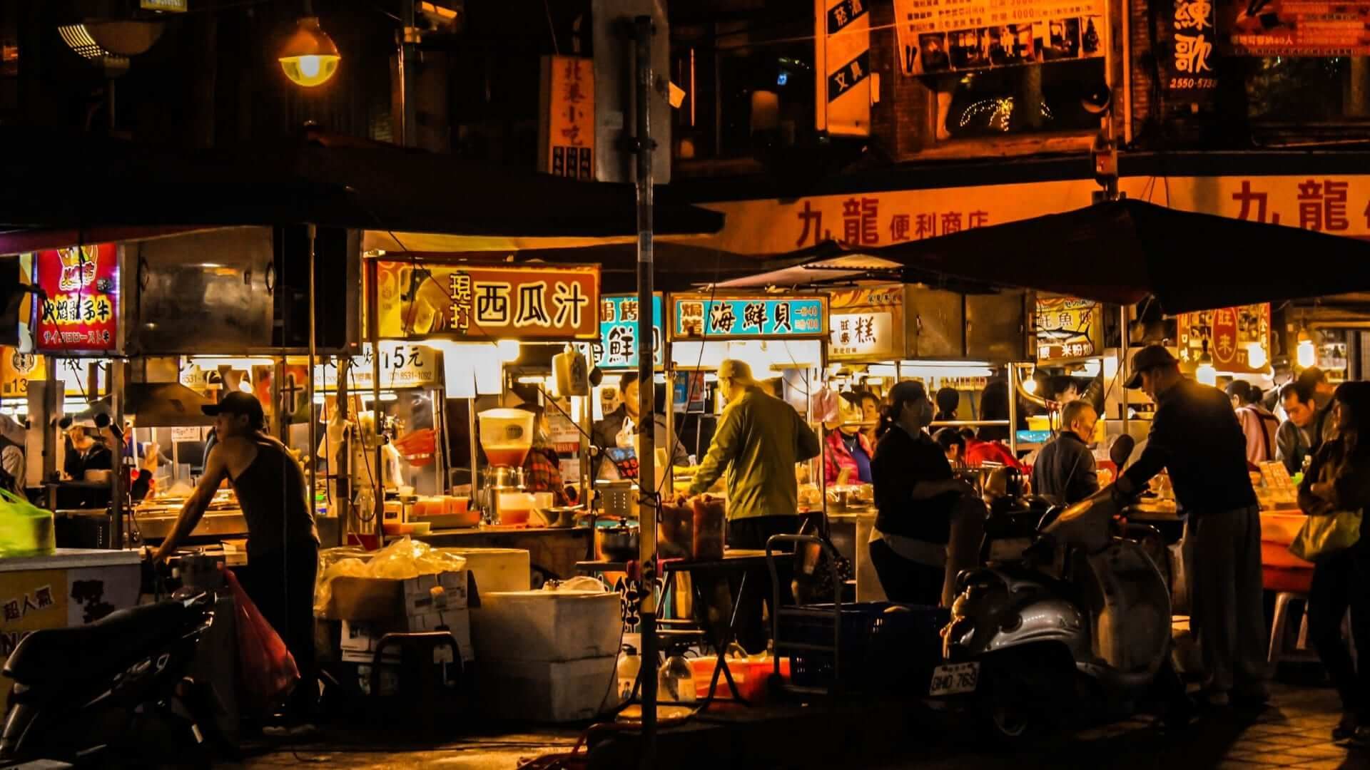 People are buying street food at a night market in Taipei.