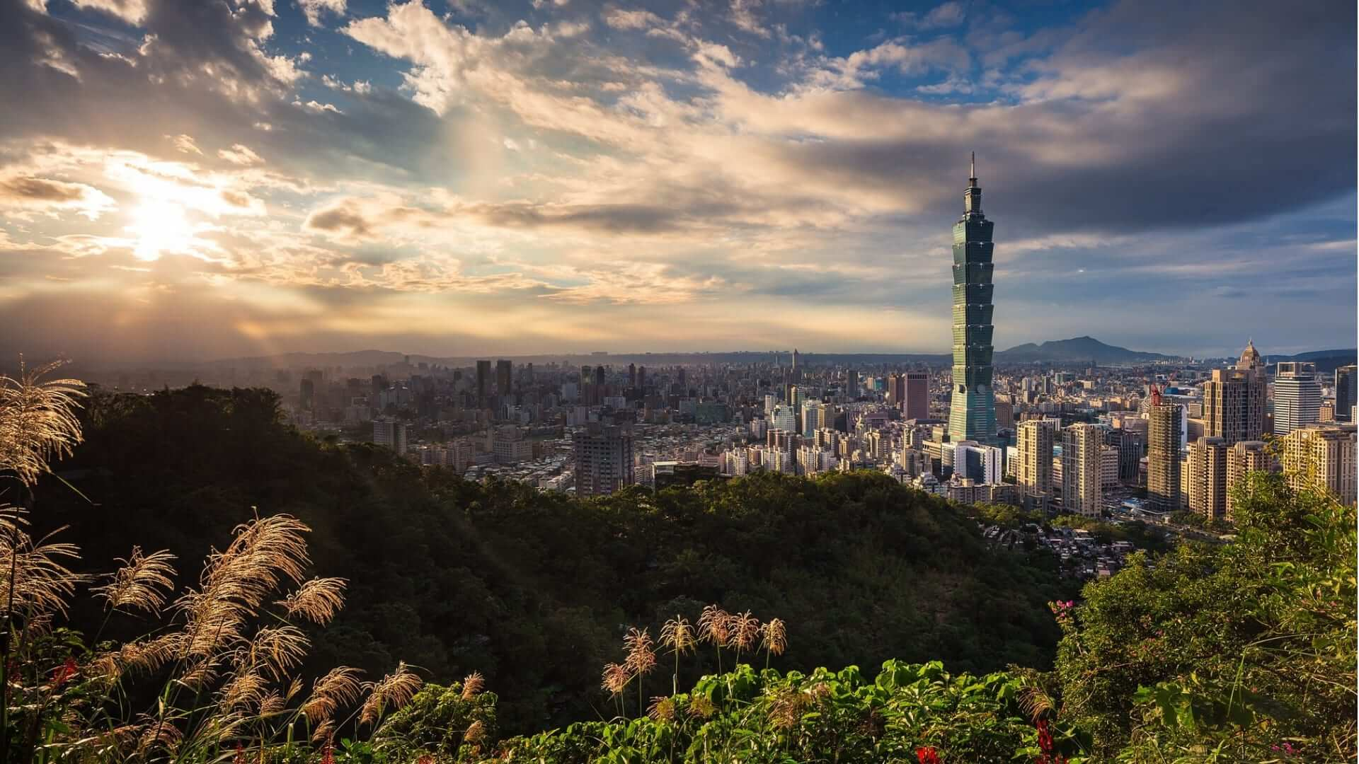 The sun shines through the clouds over Taipei and mountains and a large tower in Taiwan.